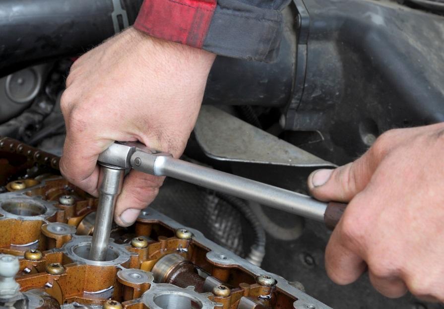 Mains d'homme qui bricole un moteur