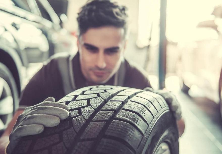 Un homme qui tient un pneu