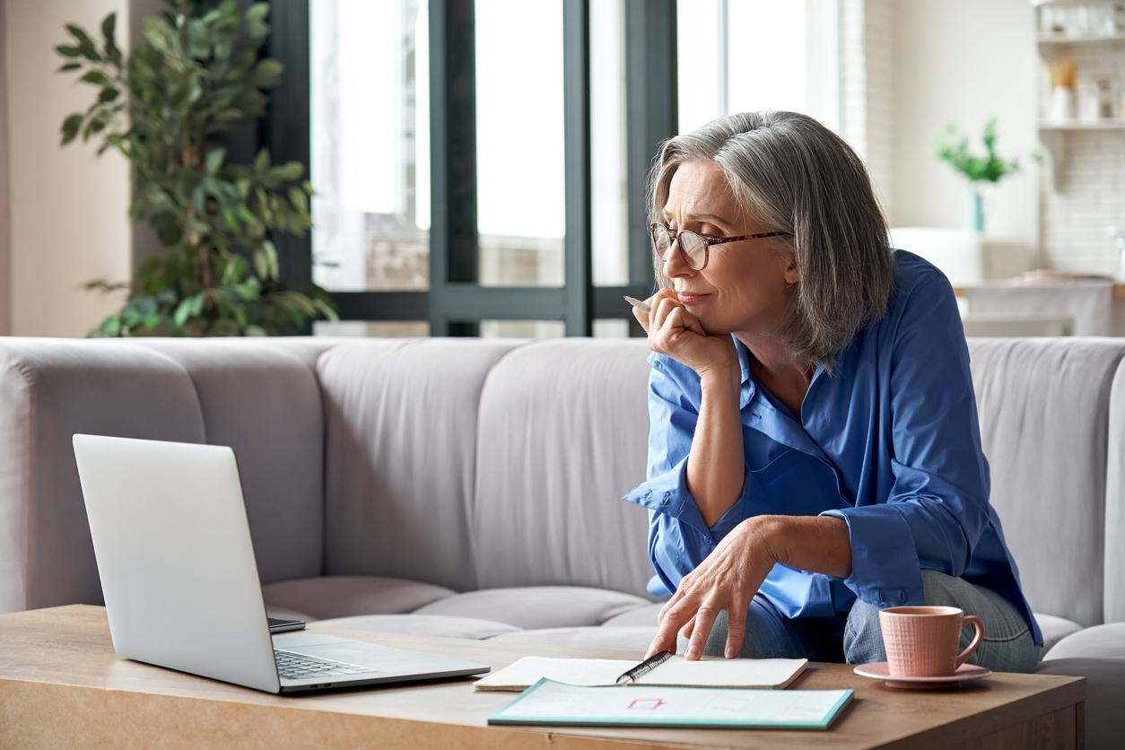 Une femme devant son ordinateur avec des papiers entrain de choisir son assurance auto