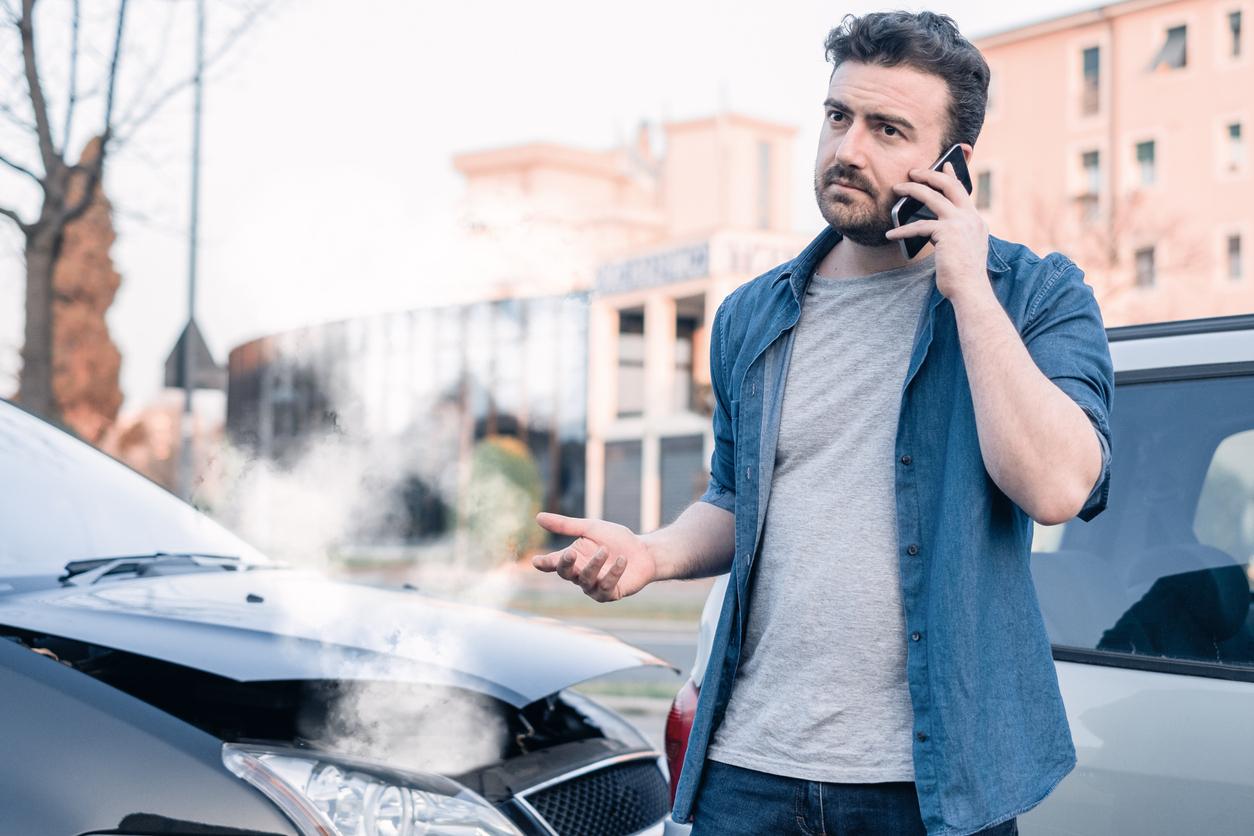 Un homme au téléphone a coté du capot de sa voiture qui fume