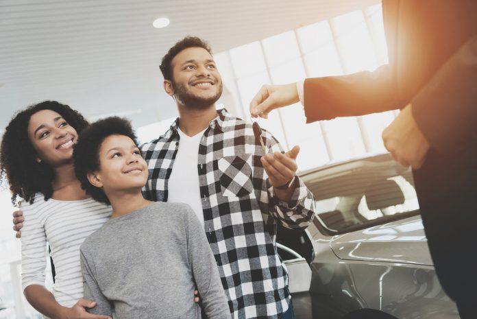 un vendeur donnant les clefs voiture à une famille